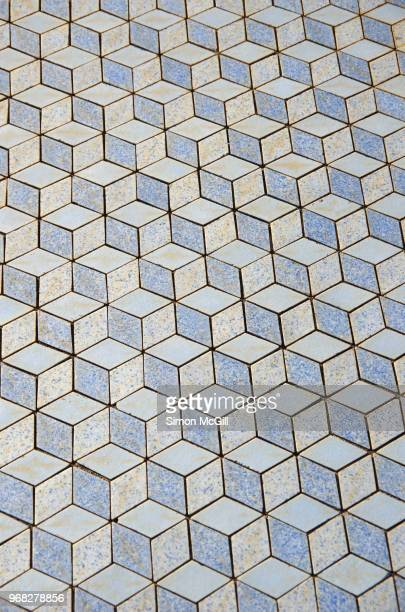 Floor tiles in a pastel blue 3D-effect isometric cube pattern
