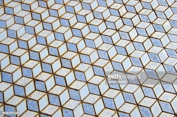 Floor tiles in a pastel blue 3D-effect isometric cube pattern