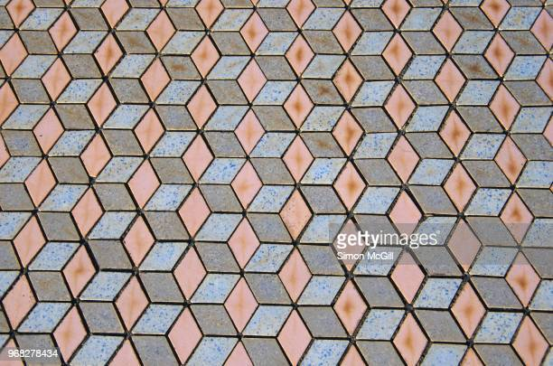 Floor tiles in a pastel blue, pink and gray 3D-effect isometric cube pattern