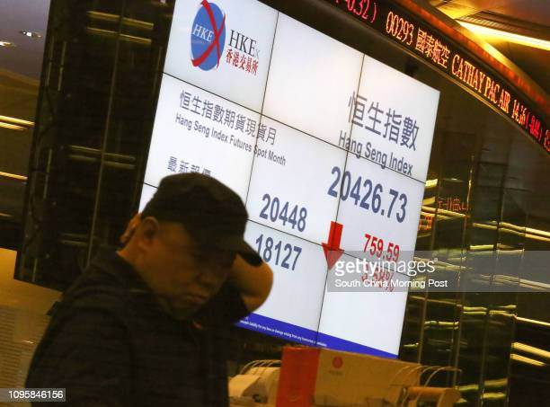Floor traders take a break at the Hong Kong Stock Exchange while the Hang Seng index slumped in the morning session 29SEP15