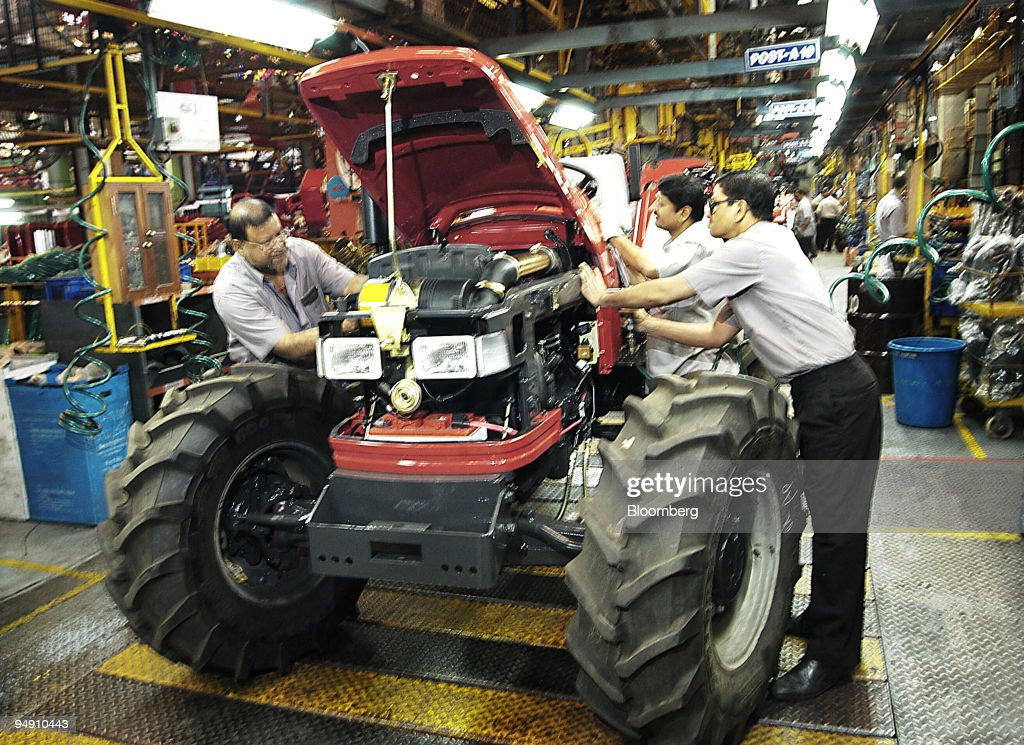 Floor Workers On The Production Line Perform Checks During Final Assembly Of A Tractor At Mahindra