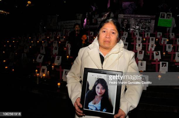 Flor Meza mother of a victim holds a picture of her daughter during a protest of the 'Los Machos Nos Matan En Mexico' movement to demand justice for...