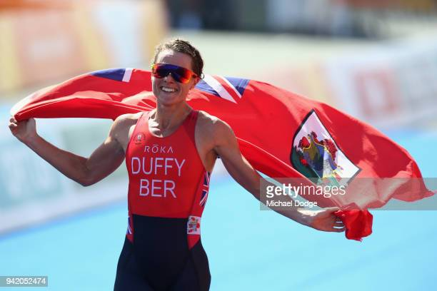 Flora Duffy of Bermuda celebrates on her way to winning gold during the Women's Triathlon on day one of the Gold Coast 2018 Commonwealth Games at...