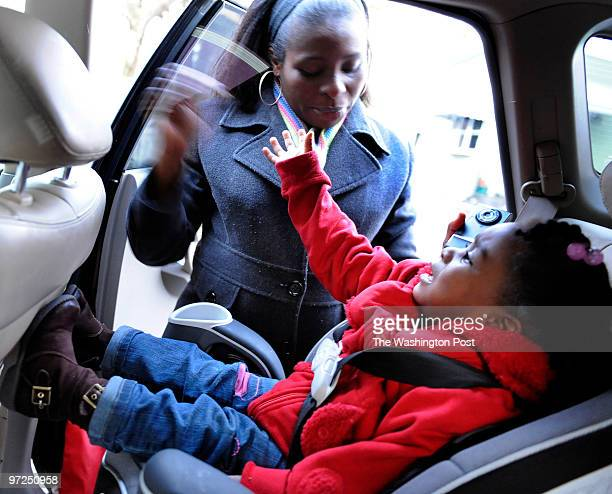 Flora Izuka played with her daughter Amara Mbah after placing her in the car seat outside at the World Child Development Center on February 23 2010...