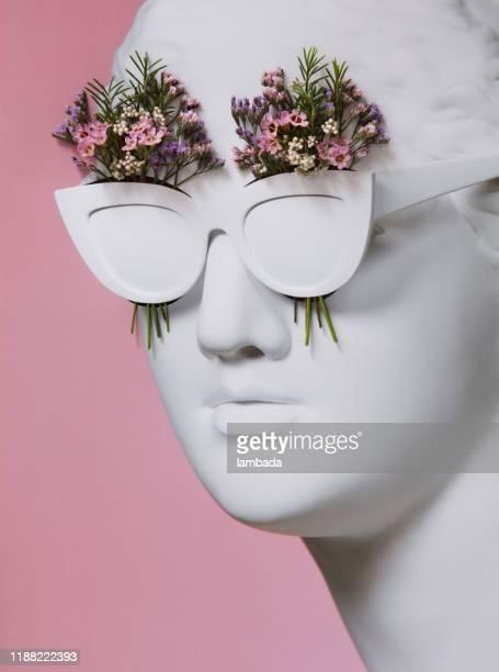 サングラスをかけたギリシャの女神との花のコラージュ - 彫刻物 ストックフォトと画像