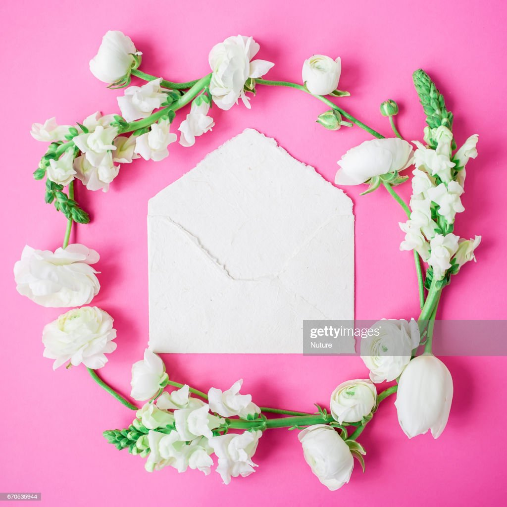 Floral Frame Of White Flowers And Paper Envelope On Pink Background