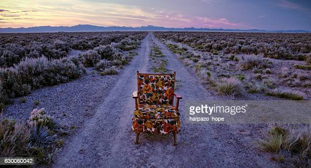 floral patterned chair on an empty dirt road. - out of context stock pictures, royalty-free photos & images