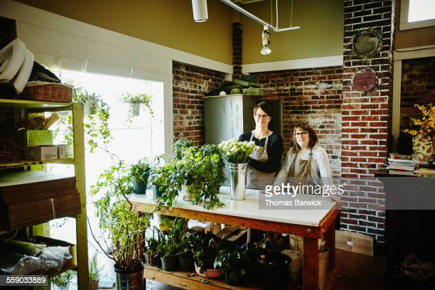 Floral shop owners standing at workbench in shop