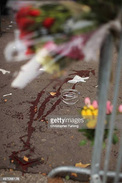 A floral tribute is placed next to blood stains near the scene of the Bataclan Theatre terrorist attack on November 14 2015 in Paris France At least...