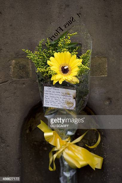 A floral tribute tied with a yellow ribbon is placed on the Eccles Cross for murdered aid worker Alan Henning in Eccles north west England on October...
