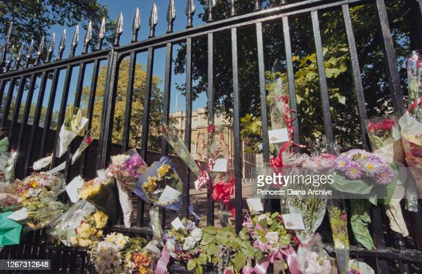 Floral tributes and messages of condolence in memory of British Royal Diana Princess of Wales are left on railings outside Buckingham Palace in...