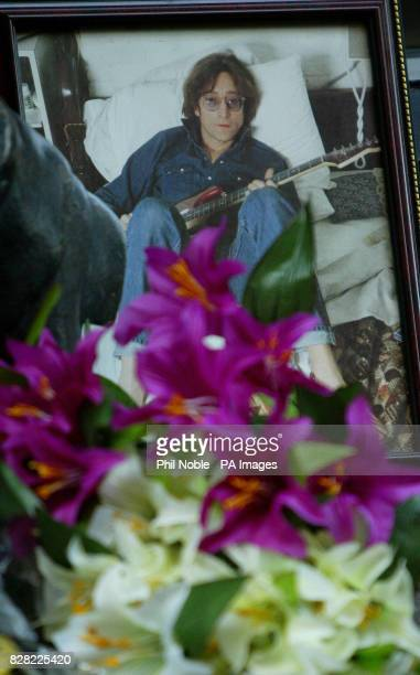 Floral tributes and photos are laid near to a statue of The Beatles in the Cavern Walk shopping centre in Liverpool on the 25th anniversary of the...