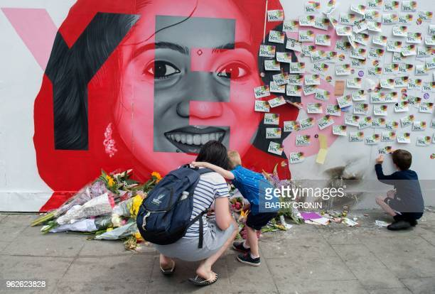 TOPSHOT Floral tributes are laid at a mural to Savita Halappanavar a 31yearold Indian dentist who died in 2012 due to the complications of a septic...