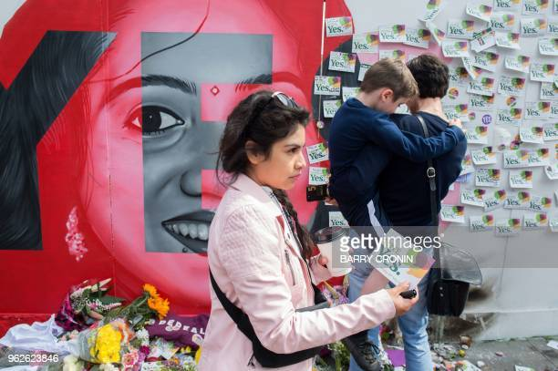 Floral tributes are laid at a mural to Savita Halappanavar a 31yearold Indian dentist who died in 2012 due to the complications of a septic...