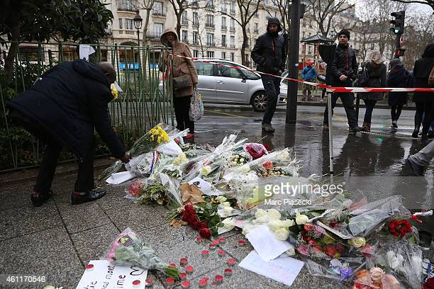Floral tributes are left close to the Charlie Hebdo offices on a day of mourning following a terrorist attack on the satirical newspaper building on...