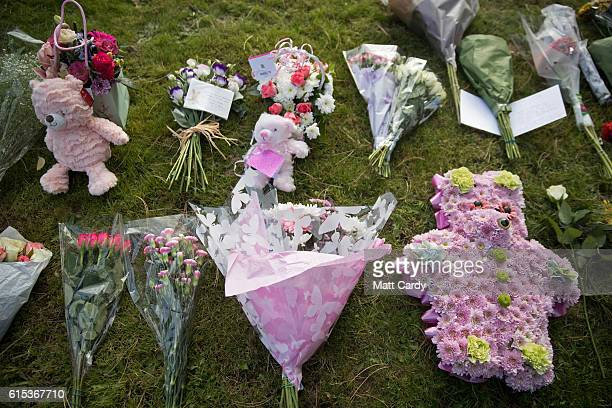 Floral tributes are left close to the graveside at the funeral of a baby girl who was found dead on a footpath earlier this year at Wolvercote...