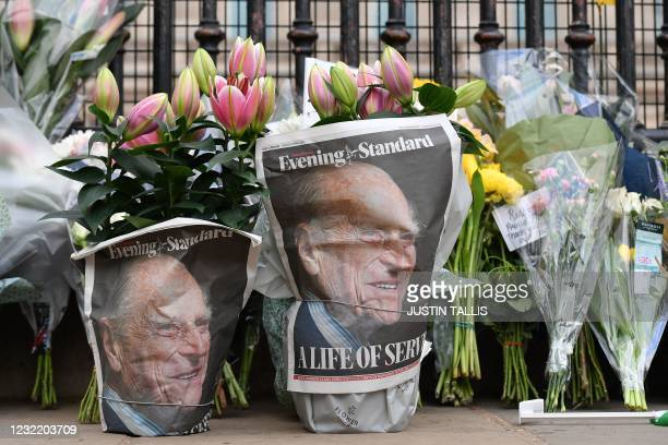 Floral tributes are pictured at the gates of Buckingham Palace in central London on April 9, 2021 after the announcement of the death of Britain's...