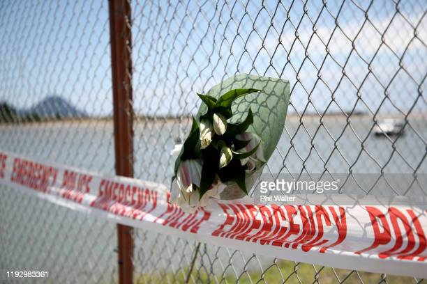 Floral tributes are placed on a fence at the Whakatane Wharf on December 10 2019 in Whakatane New Zealand 5 people are confirmed dead and several are...