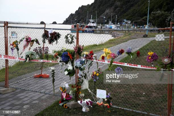 Floral tributes are placed on a security fence on the Whakatane Wharf on December 11 2019 in Whakatane New Zealand Six people are confirmed dead and...
