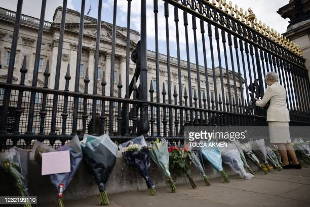 Floral tributes are seen against the railings at the front of Buckingham Palace in central London on April 9, 2021 after the announcement of the...
