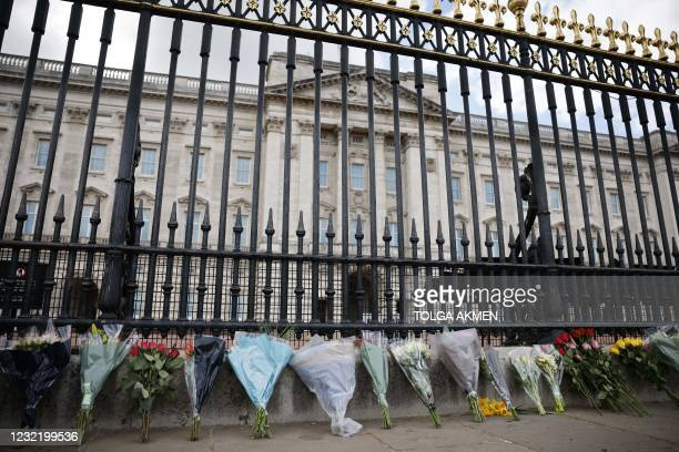 Floral tributes are seen laid against the railings at the front of Buckingham Palace in central London on April 9, 2021 after the announcement of the...