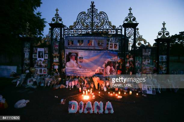 TOPSHOT Floral tributes candels and photographs are seen left outside one of the entrances of Kensington Palace in London on August 31 to mark the...