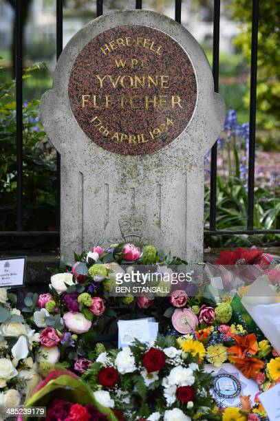 floral tributes cluster around a memorial stone at the spot where British police officer Yvonne Fletcher was killed during a remembrance service to...
