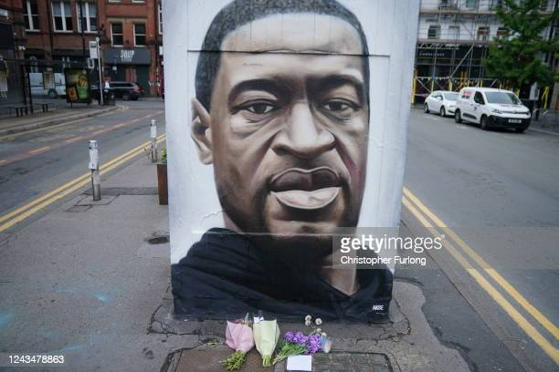 Floral tributes lay next to a mural of George Floyd, by street artist Akse, in Manchester's northern quarter on June 03, 2020 in Manchester, United...