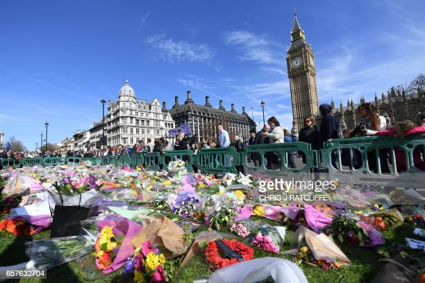 Floral tributes left in honour of the victims of the London terror attack on March 22 are pictured in Parliament Square in Westminster central London...