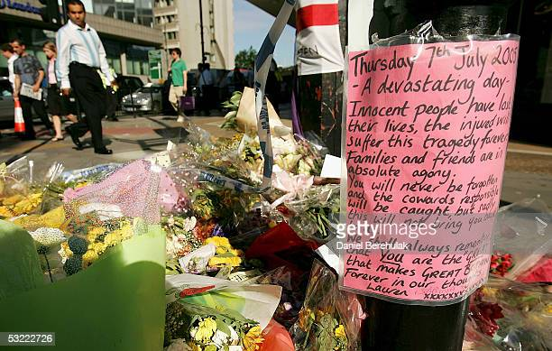 Floral tributes lie outside Edgware Road underground station as police patrol outside on July 11 2005 London England A massive police investigation...