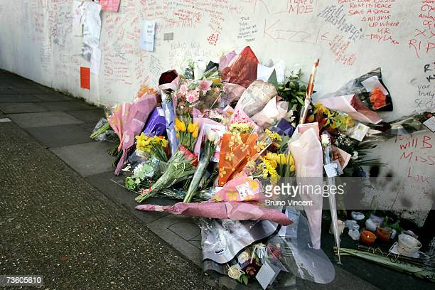 Floral tributes scatter the ground beneath lyrics and tributes written by friends of the murdered teenager Kodjo Yenga decorate a wall near to where...