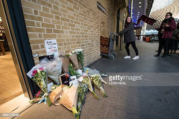 Floral tributes to British actor Alan Rickman are seen as people pose at the Platform 9 3/4 Harry Potter display at King's Cross station in London on...