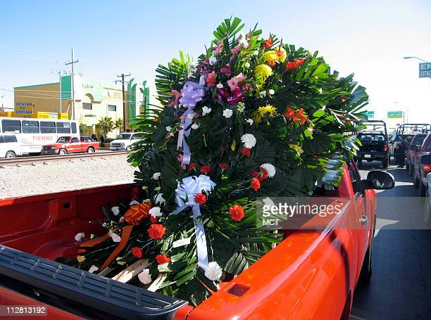 A floral wreath for the latest police officer slain in Ciudad Juarez nearly fills the bed of a pickup truck