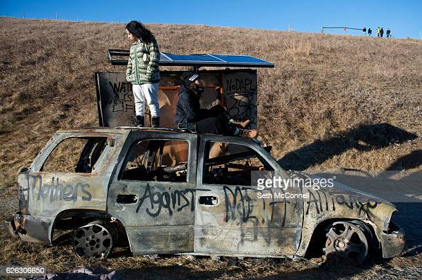 Florcy Romero left and Ewok Gia stand and sit on the top of a burned out car along Highway 1806 near the Oceti Sakowin Camp on the Standing Rock...