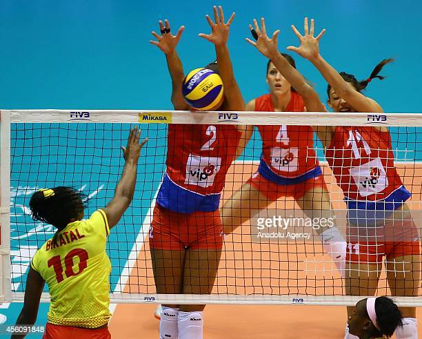 Flore Bikatal of Cameroon in action against Brakocevic and Veljkov of Serbia during the 2014 FIVB Volleyball Women's World Championship Group B...