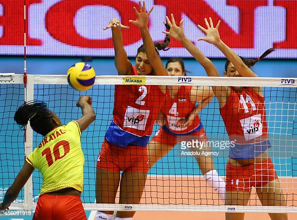 Flore Bikatal of Cameroon in action against Brakocevic and Veljkovic of Serbia during the 2014 FIVB Volleyball Women's World Championship Group B...