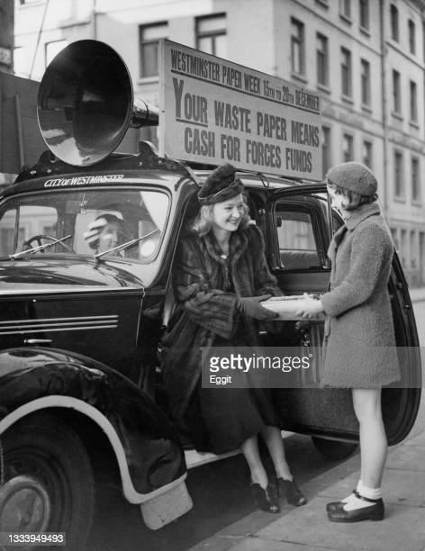 Florence Desmond , English actress, comedian and impersonator receives a bundle of waste paper materials from a young girl to recycle for the...