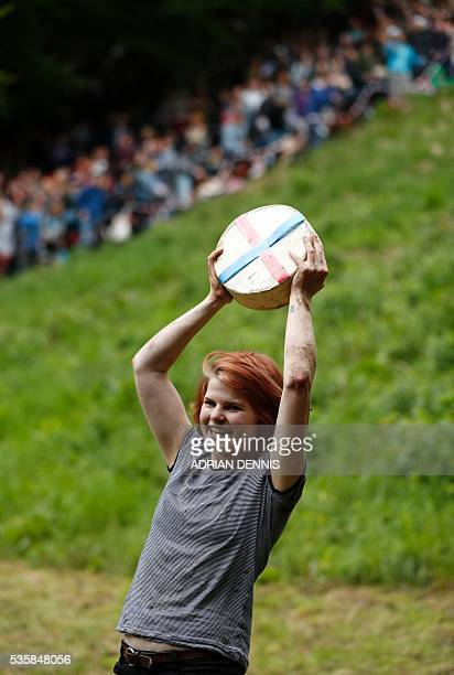 Florence Early holds her cheese aloft after winning the women's race in the annual Cooper's Hill cheese rolling competition near the village of...