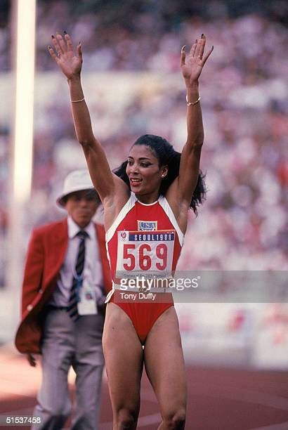 Florence Griffith Joyner of the USA waves at the crowd as she celebrates setting a new Olympic record to win the gold medal in the Women's 100 meters...