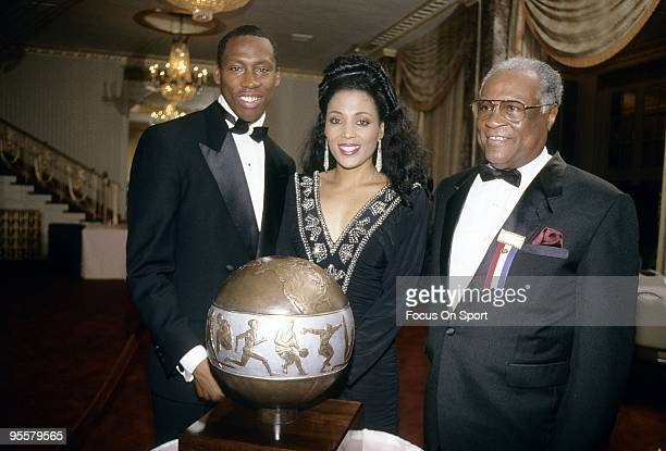 Florence Griffith Joyner with her husband AL Joyner posing with the 'Jesse Owens International Awards Trophy' presented to her by the International...