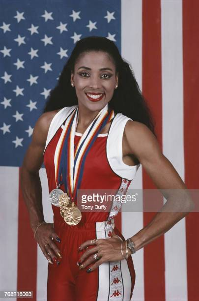 Florence GriffithJoyner poses for a portrait in front of the Stars and Stripes flag of theUnited States with her medals for winning gold in the...