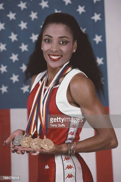 Florence Griffith-Joyner poses for a portrait in front of the Stars and Stripes flag of theUnited States with her medals for winning gold in the...