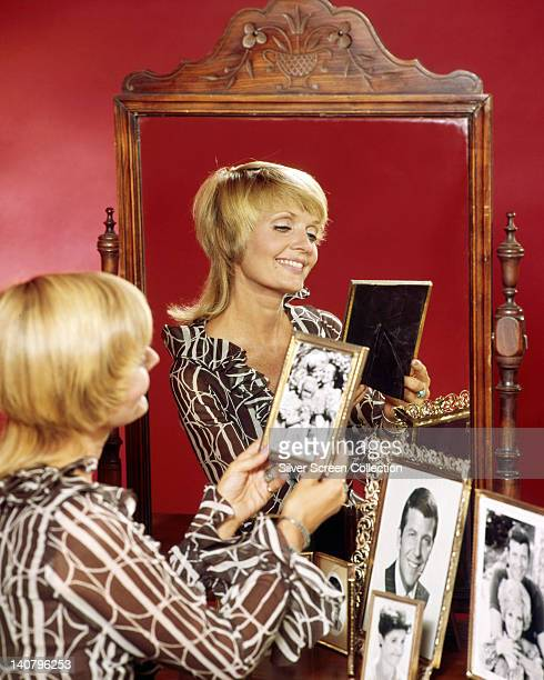 Florence Henderson US actress admiring photographs in frames on a table with a large mirror which reflects Henderson in a portrait issued as...