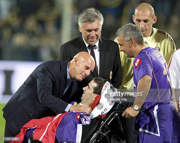 Arrigo Sacchi Carlo Ancelotti Stefano Borgonovo and Roberto Baggio greet a fan during the Match for Borgonovo in Florence Italy