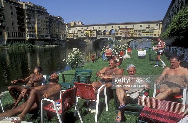Florence Italy In 1996 Members of the Florence rowing club resting in front of the Ponte Vecchio on the bank of the Arno
