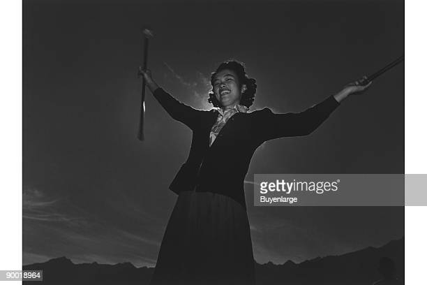 Florence Kuwata threequarter length portrait standing arms outstretched holding a baton in each hand Ansel Easton Adams was an American photographer...