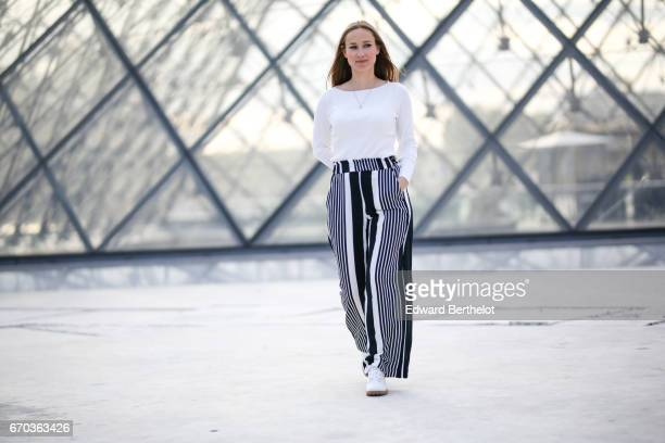 Florence Maninet wears a white top and striped pants at the Louvre on April 16 2017 in Paris France