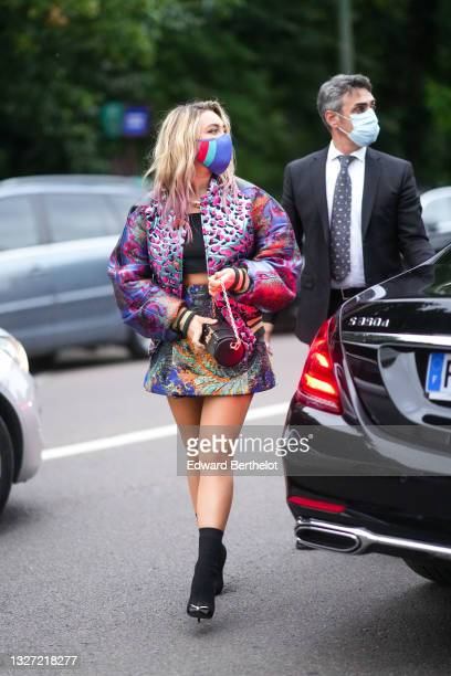 Florence Pugh wears a gold large chain necklace from Louis Vuitton, a black crop-top / t-shirt, a blue shiny with pink fuchsia and black leopard...