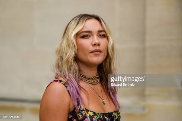 Florence Pugh wears gold pendant earrings, a gold J'Adior chain necklace, a multicolored pearls necklace, gold necklace, a black tulle with...