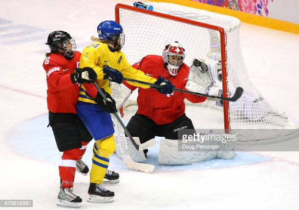 Florence Schelling of Switzerland makes a glove save against Erika Grahm of Sweden as Julia Marty of Switzerland defends during the Ice Hockey...